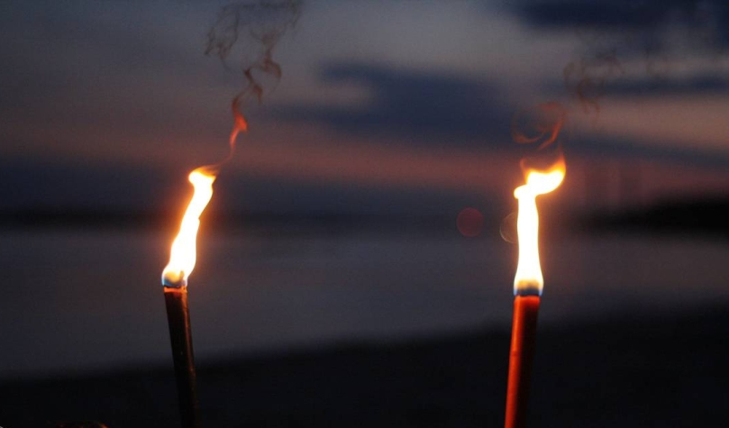 Two torches shining in the darkness with water in the backgrond