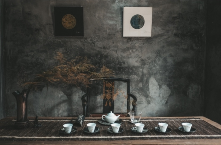The image shows a table set with six teacups, a teapot and a glass beaker. The wall at the back is adorned with oriental art and a flower arrangement.