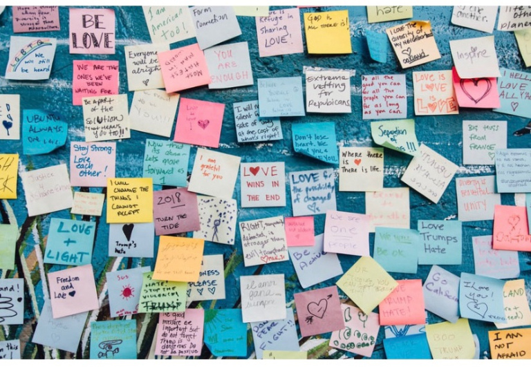 The image shows a board covered with hand written messages about love.