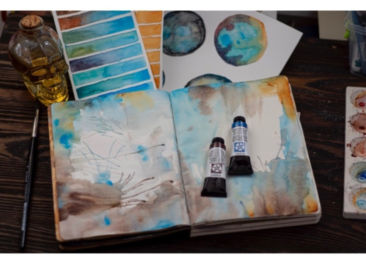The image shows an incomplete watercolor on open pages of a notebook. There are tubes of colors next to it and some painting paraphernalia.