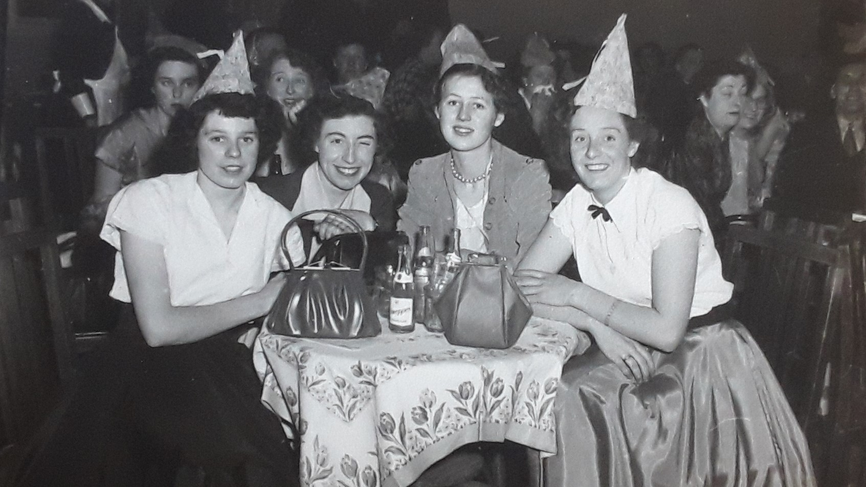 an old photo taken c. 1960 showing four young women all dressed up sitting at a table with their handbags in front of them. You can see little bottles of tonic water, but the accompanying gin is hidden.